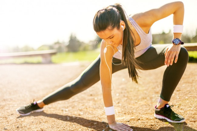 Beutiful young woman stretching and preparing to run.